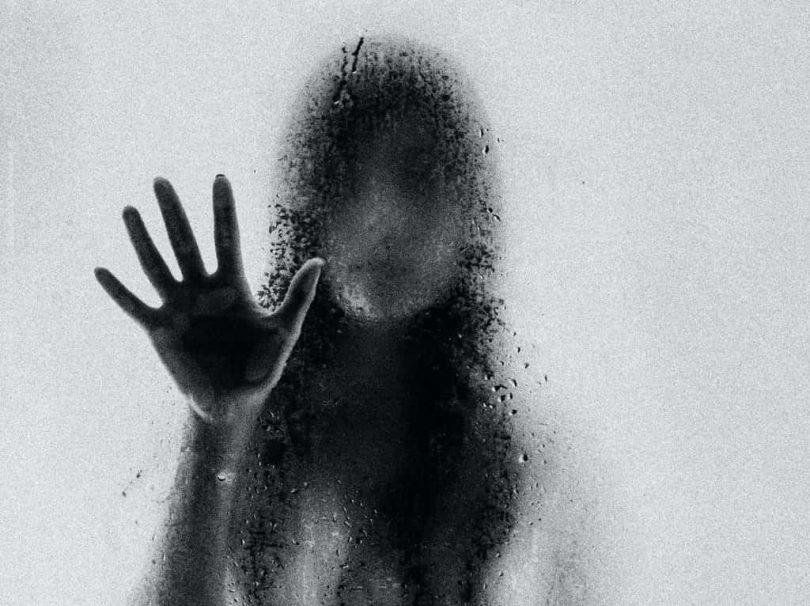 Image of a ghostly woman behind a window pane