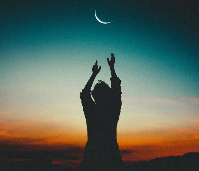 Image of a person reaching for the moon at sunset
