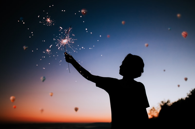Image of a boy at sunset with a sparkler