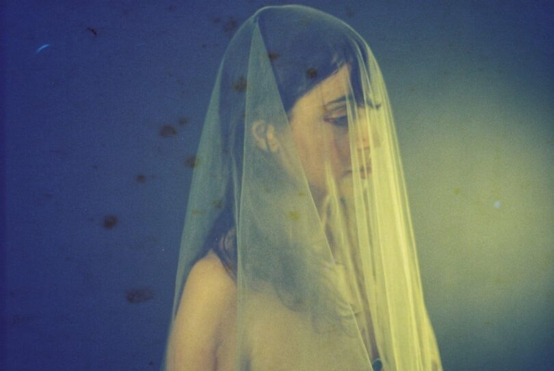 Image of a sad woman struggling with self-forgiveness with a veil over her head