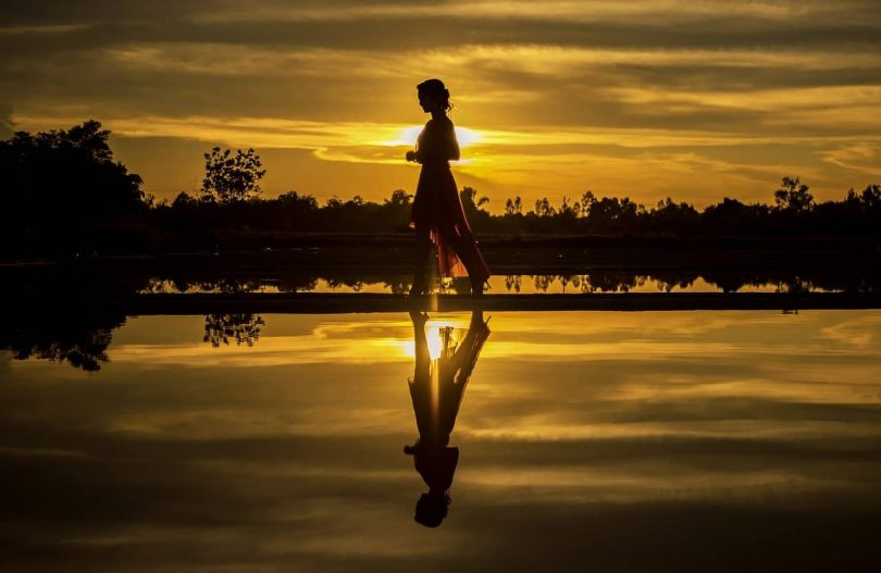 Image of a woman walking along the river at sunset