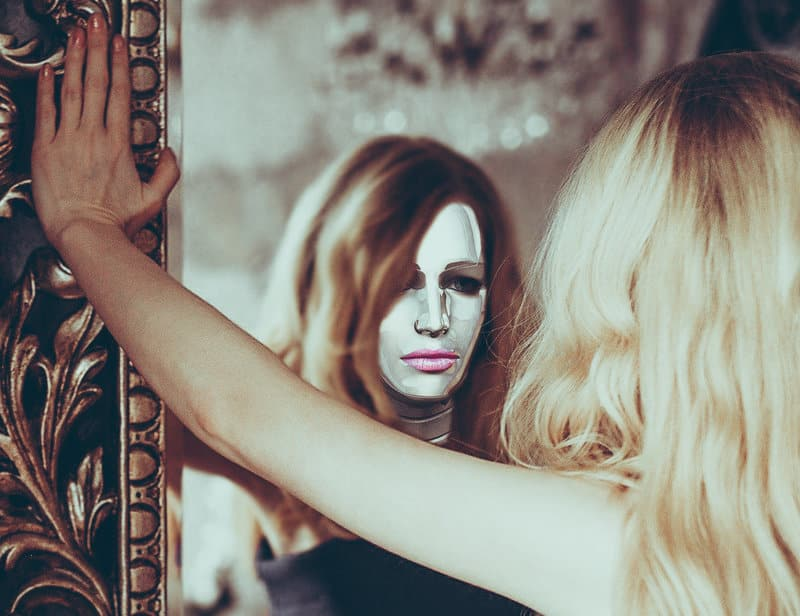 Image of a woman wearing a mask looking at herself in the mirror