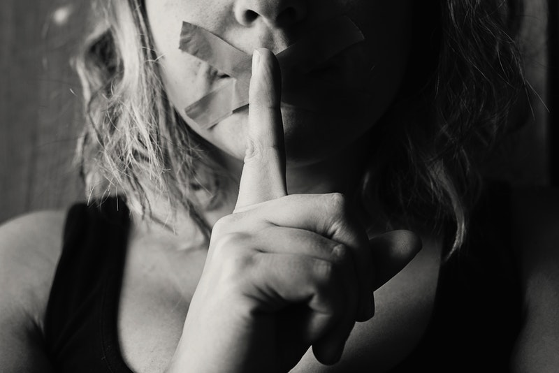 Image of a woman with tape over her mouth
