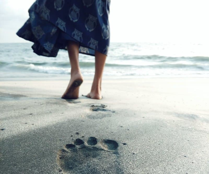 Image of a woman walking on the beach grounding herself