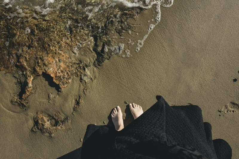 Image of a woman's feet on the beach near the water