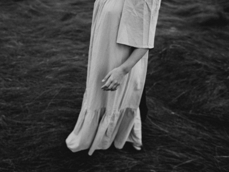 Image of a woman in a white dress in a paddock