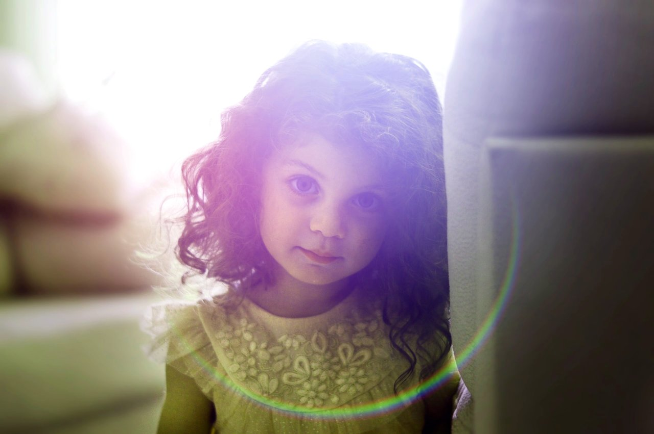 Image of a curious little girl with the sun behind her symbolic of the inner child