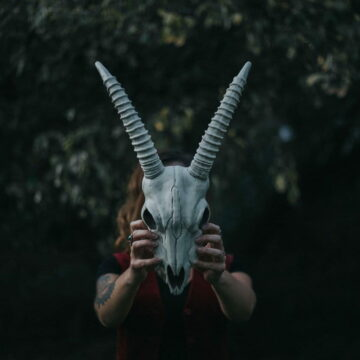 Image of a woman holding up an animal skull symbolic of the collective shadow
