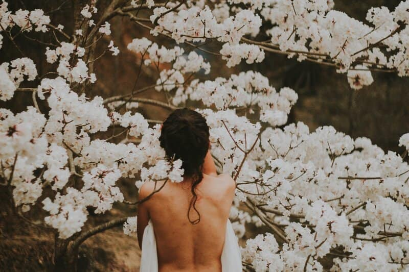 Image of a woman standing in front of white flowers