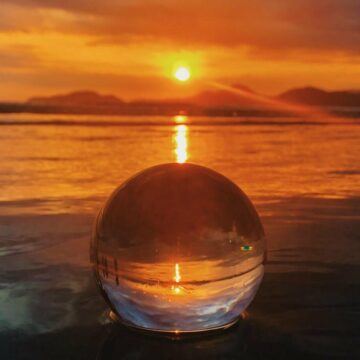 Image of a glass ball in front of a sunset symbolic of our true nature