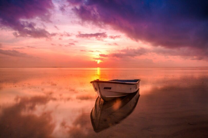 Image of a boat at dawn in a peaceful ocean symbolic of healing meditation