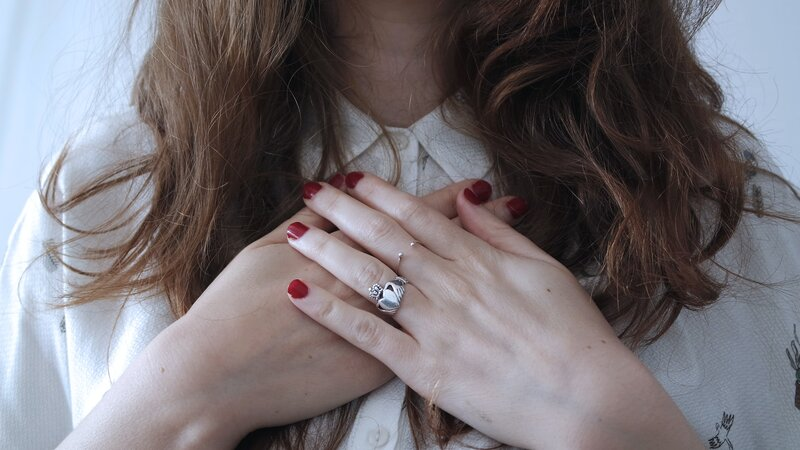 Image of a woman with hands over her heart