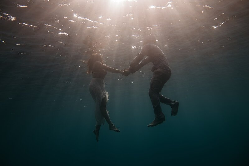 Image of two people holding hands stranded in the ocean