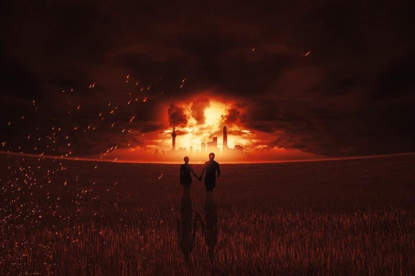 Image of a couple holding hands while a city burns symbolic of karmic relationship
