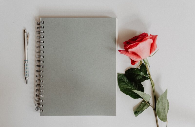 Image of a grey journal next to a pink rose