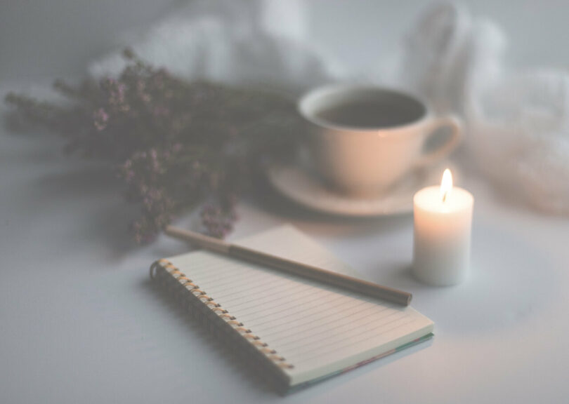 Image of a notebook journal, candle, and cup of tea
