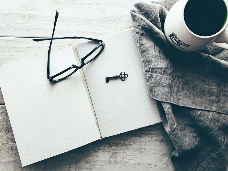 Image of an open journal next to a cup of coffee