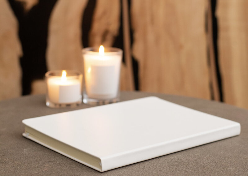 Image of a white journal on a table with candles in the background