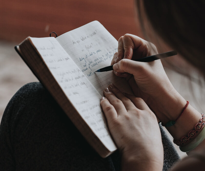 Image of a woman writing in a journal