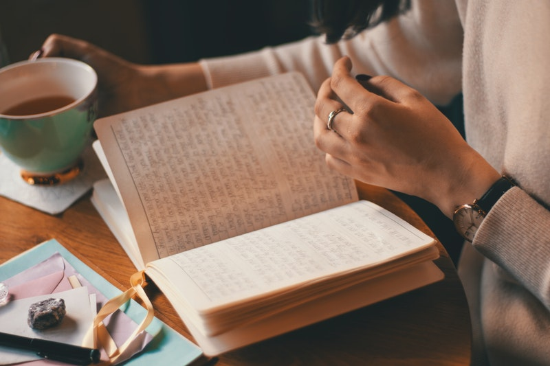 Image of a woman flipping through pages of her journal