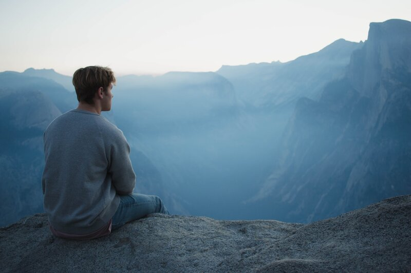 Image of a man practicing spiritual meditation overlooking some blue mountains