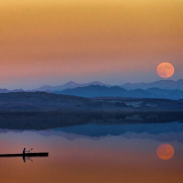 Image of a beautiful sunset with a person on a boat practicing spiritual meditation