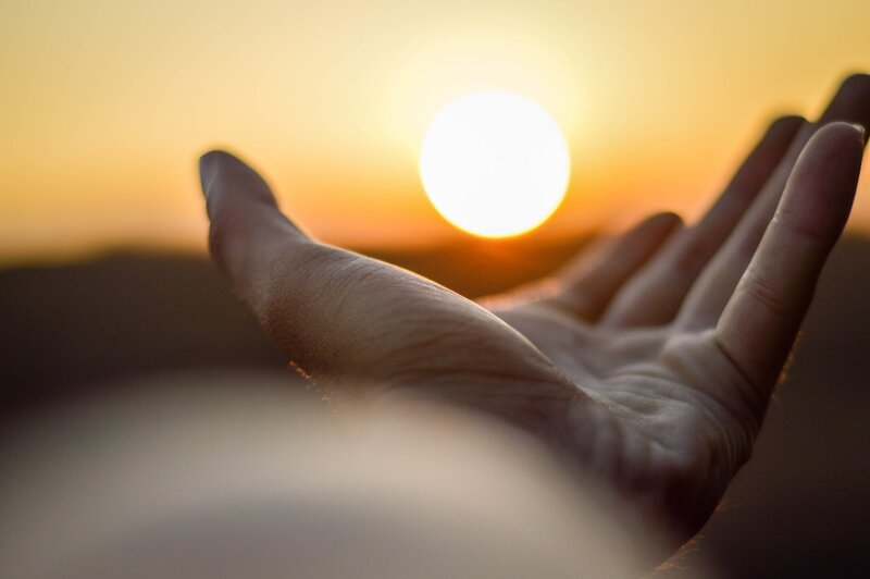 Image of a man reaching out toward the sun