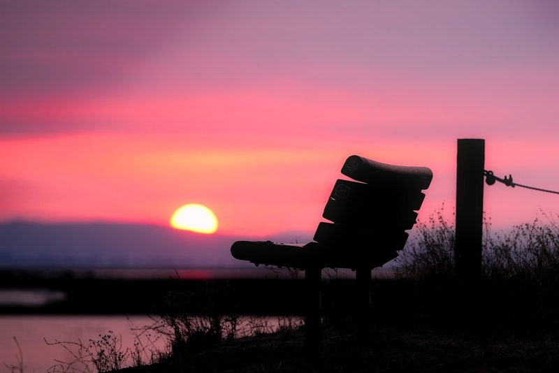 Image of a solitary seat facing the pink sunset