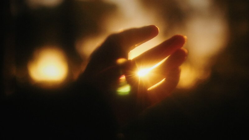 Image of a hand reaching for the sunlight symbolic of finding one's soul purpose in life